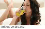 Купить «Brunette haired woman drinking orange juice», видеоролик № 29680662, снято 11 ноября 2011 г. (c) Wavebreak Media / Фотобанк Лори
