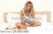 Купить «Blonde haired woman having her breakfast while reading», видеоролик № 29680666, снято 11 ноября 2011 г. (c) Wavebreak Media / Фотобанк Лори