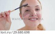 Купить «Smiling blonde woman brushing her eyebrows», видеоролик № 29680698, снято 22 ноября 2011 г. (c) Wavebreak Media / Фотобанк Лори