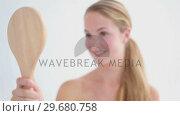 Купить «Smiling blonde woman holding a mirror», видеоролик № 29680758, снято 22 ноября 2011 г. (c) Wavebreak Media / Фотобанк Лори