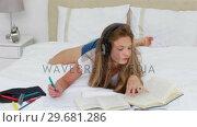 Купить «Young woman listening to music while doing her homework», видеоролик № 29681286, снято 23 ноября 2011 г. (c) Wavebreak Media / Фотобанк Лори