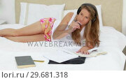 Купить «Young brunette woman studying while listening to music», видеоролик № 29681318, снято 23 ноября 2011 г. (c) Wavebreak Media / Фотобанк Лори