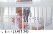 Купить «Woman giving dolls to a baby», видеоролик № 29681546, снято 25 ноября 2011 г. (c) Wavebreak Media / Фотобанк Лори