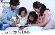Купить «Family reading a ebook between them», видеоролик № 29681846, снято 25 ноября 2011 г. (c) Wavebreak Media / Фотобанк Лори