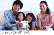 Купить «Family watching television while eating popcorn», видеоролик № 29681870, снято 25 ноября 2011 г. (c) Wavebreak Media / Фотобанк Лори