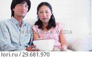 Купить «Couple eating popcorn together», видеоролик № 29681970, снято 25 ноября 2011 г. (c) Wavebreak Media / Фотобанк Лори