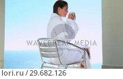 Купить «Woman drinking a coffee with a sea view», видеоролик № 29682126, снято 7 ноября 2011 г. (c) Wavebreak Media / Фотобанк Лори