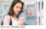 Купить «Client in a pharmacy holding a bottle of drug», видеоролик № 29682202, снято 26 апреля 2012 г. (c) Wavebreak Media / Фотобанк Лори