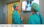 Купить «Two surgeons examining a Xray», видеоролик № 29682502, снято 24 апреля 2012 г. (c) Wavebreak Media / Фотобанк Лори