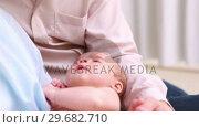 Купить «Smiling man and woman holding a new born baby», видеоролик № 29682710, снято 27 апреля 2012 г. (c) Wavebreak Media / Фотобанк Лори