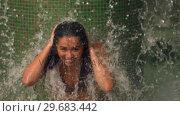 Купить «Woman touching hair under a tropical shower», видеоролик № 29683442, снято 2 октября 2012 г. (c) Wavebreak Media / Фотобанк Лори