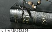 Купить «Rosary beads falling onto a bible », видеоролик № 29683834, снято 18 января 2013 г. (c) Wavebreak Media / Фотобанк Лори