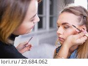 Купить «Makeup artist applying make up on alluring model.», фото № 29684062, снято 19 марта 2016 г. (c) Сергей Сухоруков / Фотобанк Лори