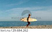 Купить «Woman running on the beach with her surfboard», видеоролик № 29684262, снято 26 марта 2013 г. (c) Wavebreak Media / Фотобанк Лори
