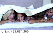 Family lying under the covers and chatting. Стоковое видео, агентство Wavebreak Media / Фотобанк Лори