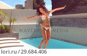 Купить «Pretty woman leaping beside swimming pool», видеоролик № 29684406, снято 25 марта 2013 г. (c) Wavebreak Media / Фотобанк Лори