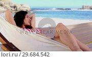 Купить «Pretty girl sunbathing in a hammock», видеоролик № 29684542, снято 3 апреля 2013 г. (c) Wavebreak Media / Фотобанк Лори
