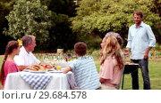 Купить «Family eating outdoors», видеоролик № 29684578, снято 5 апреля 2013 г. (c) Wavebreak Media / Фотобанк Лори