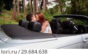 Купить «Woman kissing her boyfriend in a convertible car», видеоролик № 29684638, снято 6 апреля 2013 г. (c) Wavebreak Media / Фотобанк Лори