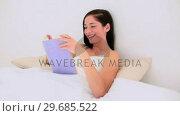 Купить «Attractive brunette reading a book in bed», видеоролик № 29685522, снято 10 июля 2013 г. (c) Wavebreak Media / Фотобанк Лори