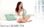 Купить «Lovely young woman phoning with her smartphone while sitting on her bed», видеоролик № 29685774, снято 24 июля 2013 г. (c) Wavebreak Media / Фотобанк Лори