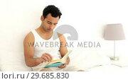Купить «Happy handsome man reading a book», видеоролик № 29685830, снято 8 августа 2013 г. (c) Wavebreak Media / Фотобанк Лори
