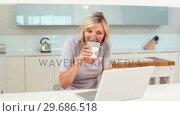 Купить «Blonde woman drinking coffee while using her laptop», видеоролик № 29686518, снято 17 октября 2013 г. (c) Wavebreak Media / Фотобанк Лори