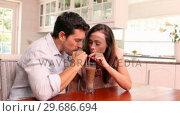 Купить «Happy couple drinking a milkshake together», видеоролик № 29686694, снято 12 декабря 2013 г. (c) Wavebreak Media / Фотобанк Лори