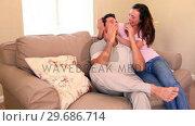 Купить «Woman sitting down on couch covering her boyfriends eyes», видеоролик № 29686714, снято 12 декабря 2013 г. (c) Wavebreak Media / Фотобанк Лори