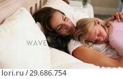 Купить «Mother and daughter sleeping together in bed», видеоролик № 29686754, снято 13 декабря 2013 г. (c) Wavebreak Media / Фотобанк Лори