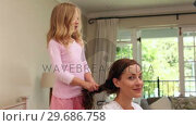 Little girl plaiting her mothers hair in the morning. Стоковое видео, агентство Wavebreak Media / Фотобанк Лори