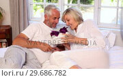 Купить «Man surprising his partner with a gift on bed», видеоролик № 29686782, снято 6 декабря 2013 г. (c) Wavebreak Media / Фотобанк Лори