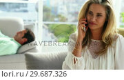 Young woman talking on mobile phone in living room at home. Стоковое видео, агентство Wavebreak Media / Фотобанк Лори