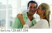 Smiling woman kissing on mans cheek in living room at home. Стоковое видео, агентство Wavebreak Media / Фотобанк Лори