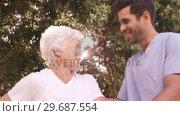 Купить «Male nurse assisting a senior woman to walk in the backyard », видеоролик № 29687554, снято 2 марта 2016 г. (c) Wavebreak Media / Фотобанк Лори