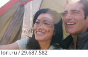 Купить «Smiling couple sitting in tent», видеоролик № 29687582, снято 9 февраля 2016 г. (c) Wavebreak Media / Фотобанк Лори