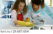 Купить «Mother assisting daughter in cleaning kitchen», видеоролик № 29687654, снято 19 февраля 2016 г. (c) Wavebreak Media / Фотобанк Лори