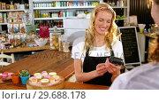 Купить «Customer making payment through payment terminal machine at counter», видеоролик № 29688178, снято 30 мая 2016 г. (c) Wavebreak Media / Фотобанк Лори