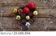 Купить «Christmas bauble, pine cone and christmas lights arranged on a plank», видеоролик № 29688894, снято 30 августа 2016 г. (c) Wavebreak Media / Фотобанк Лори