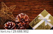 Купить «Pine cones with gift box and star shape ornament on a plank», видеоролик № 29688902, снято 30 августа 2016 г. (c) Wavebreak Media / Фотобанк Лори