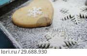 Купить «Heart shape cookies with snowflake and icing sugar on tray», видеоролик № 29688930, снято 30 августа 2016 г. (c) Wavebreak Media / Фотобанк Лори