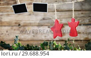 Купить «Christmas decorations hanging against wooden wall», видеоролик № 29688954, снято 30 августа 2016 г. (c) Wavebreak Media / Фотобанк Лори