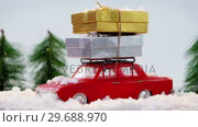Купить «Toy car carrying christmas present with fake snow», видеоролик № 29688970, снято 30 августа 2016 г. (c) Wavebreak Media / Фотобанк Лори