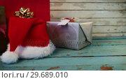 Купить «Wrapped gifts and santa hat on wooden plank», видеоролик № 29689010, снято 30 августа 2016 г. (c) Wavebreak Media / Фотобанк Лори