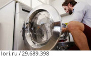 Купить «Man putting his clothes into washing machine», видеоролик № 29689398, снято 26 августа 2016 г. (c) Wavebreak Media / Фотобанк Лори