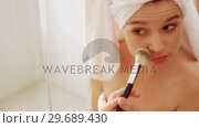 Купить «Woman applying make-up on her face in bathroom», видеоролик № 29689430, снято 26 августа 2016 г. (c) Wavebreak Media / Фотобанк Лори