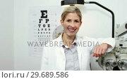 Купить «Beautiful optometrist standing in ophthalmology clinic», видеоролик № 29689586, снято 20 июня 2016 г. (c) Wavebreak Media / Фотобанк Лори