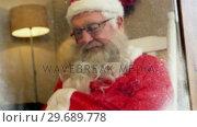 Купить «Santa claus sitting and relaxing», видеоролик № 29689778, снято 6 июня 2016 г. (c) Wavebreak Media / Фотобанк Лори
