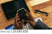 Купить «Businessman making payment online using mobile phone and credit card», видеоролик № 29689858, снято 11 августа 2016 г. (c) Wavebreak Media / Фотобанк Лори