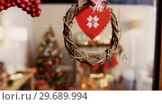 Купить «Christmas grapevine wreath with ribbon hanging on window», видеоролик № 29689994, снято 31 августа 2016 г. (c) Wavebreak Media / Фотобанк Лори